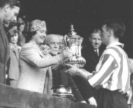 Raich Carter Receives the Cup From The Queen